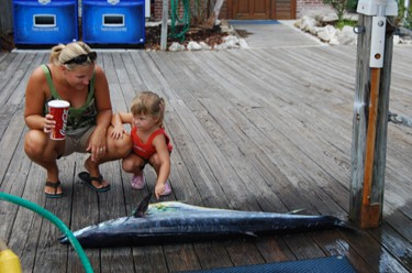 Little girl touches big wahoo-Coke in hand